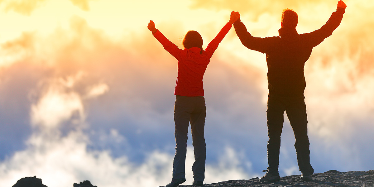 a healthy couple climbing a mountain and raising their hands to the sky in achievement