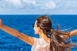 woman with arms outstretched by the sea