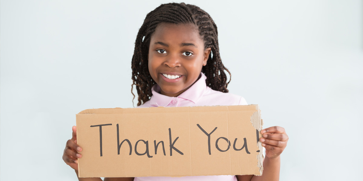 Young girl holding a sign saying thanks