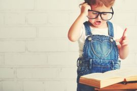 Little girl in glasses reading book