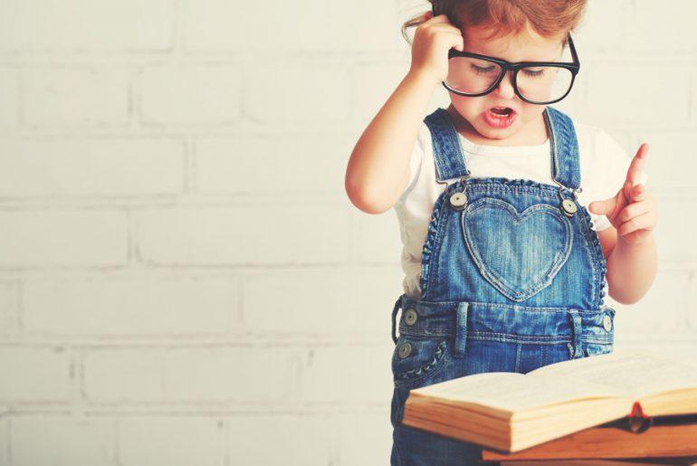 Little girl in glasses reading book